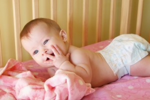 baby girl in crib with hand to face